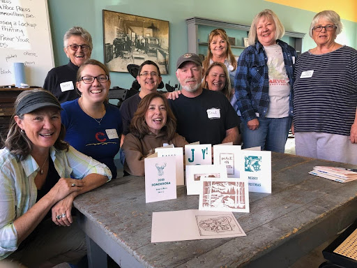 Group of adults behind a selection of holiday cards made in Mancos Common Press